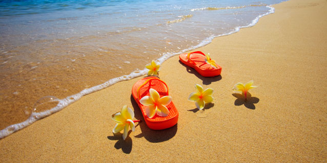 Slippers on shoreline with Plumeria flowers.